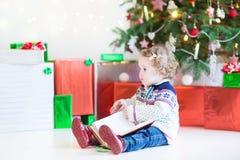 可爱的小孩女孩阅读书在圣诞树下 图库摄影