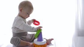 可爱的小孩男孩在明亮的屋子里演奏了教育玩具金字塔 股票视频