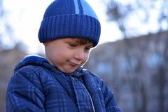 可爱的小孩男孩画象有使用与雪球的长的金发的户外 有蓝色围巾和帽子走的孩子  库存照片