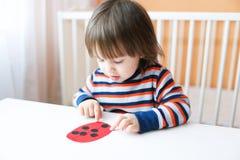 可爱的小男孩做了纸瓢虫 免版税库存照片