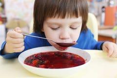 可爱的小男孩吃鲜美红色汤 免版税库存图片