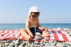 可爱的小男孩大厦小卵石在海滩耸立 免版税库存图片