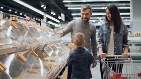 可爱的小男孩帮助他的父母选择在面包店部门的面包在食品店,他采取大面包和 股票录像