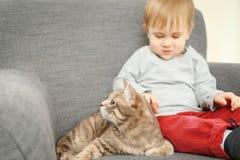 可爱的小男孩特写镜头有逗人喜爱的猫的在灰色扶手椅子 库存照片