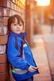 可爱的小男孩,在砖墙旁边,吃巧克力块  库存照片