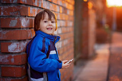 可爱的小男孩,在砖墙旁边,吃巧克力块  图库摄影