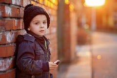可爱的小男孩,在砖墙旁边,吃巧克力块  免版税库存图片