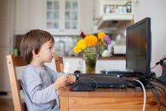 可爱的小男孩,食用棒棒糖,当观看动画片时 免版税库存图片