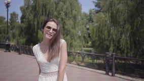 可爱的少女佩带的太阳镜和走一件长的白色夏天时尚的礼服户外 一名俏丽的妇女的休闲 影视素材