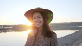 可爱的少女微笑的摆在在走的照相机在湖附近期间 股票视频