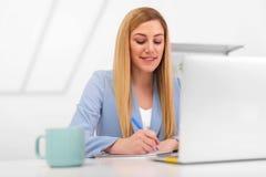 可爱的少妇与文件和膝上型计算机一起使用在工作场所在一个白色办公室 免版税库存照片