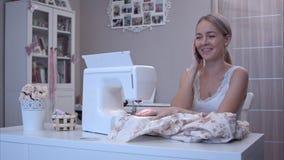 可爱的少妇回答她的电话,当缝合时 免版税库存图片