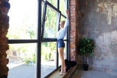 可爱的少妇在窗口sil摆在与微笑并且站立 免版税库存照片
