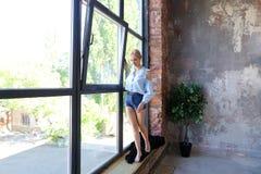 可爱的少妇在窗口sil摆在与微笑并且站立 库存照片