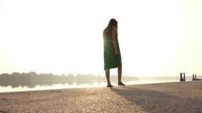 可爱的少妇在Dnipro银行的一件绿色礼服转过来 股票视频
