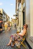 可爱的少妇坐一把黄色折叠椅 免版税库存图片