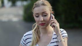 可爱的少妇愉快地走和谈话在她的流动手机在一个晴天, 股票录像