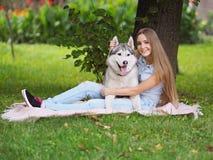 可爱的少妇拥抱在绿草的西伯利亚爱斯基摩人狗 免版税库存照片
