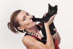 可爱的少妇拿着在手上的一只黑小猫 免版税库存照片