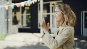 可爱的少妇摄影师在夏天拍与站立户外在美丽的城市的现代照相机的照片 股票视频