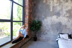可爱的少妇摆在与微笑并且坐窗口基石 免版税图库摄影