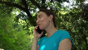 可爱的少妇由智能手机谈话在森林或公园里 股票录像