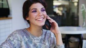 可爱的少妇谈话在电话,当坐在咖啡馆时 她微笑着 有美丽的年轻的女性偶然 影视素材