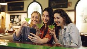 可爱的少妇采取与鸡尾酒的selfie在酒吧 快乐的女孩摆在,笑和叮当响玻璃 股票视频