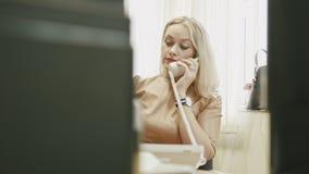 可爱的少妇-运作迷人的办公室回答电话在她的在计算机,移动式摄影车射击前面的办公室 股票视频