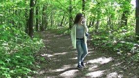 可爱的少年女孩谈话在手机,当走在美丽的春天公园时 股票录像