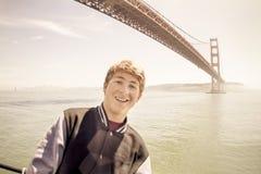 可爱的少年在金门大桥下的旧金山 免版税图库摄影