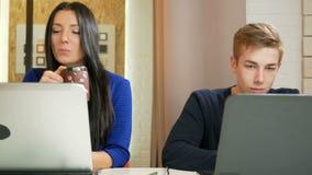 可爱的工作在膝上型计算机的办公室的妇女和一个年轻人 聚焦打印在键盘和神色在 股票录像