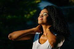 可爱的平安的非洲女孩的画象有嫉妒的遮蔽放松和享受与闭合的天气 库存照片