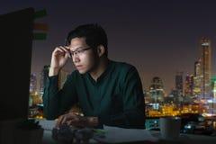 可爱的年轻亚裔人坐看在黑暗夜间运作的感觉严肃认为的书桌桌手提电脑 免版税图库摄影