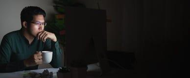 可爱的年轻亚裔人饮用的咖啡横幅坐看在黑暗的夜间工作的书桌桌手提电脑 免版税库存图片