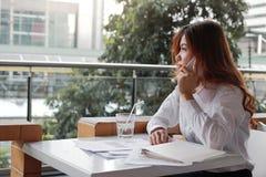 可爱的年轻亚裔女商人背面图谈话在电话在办公室 库存照片
