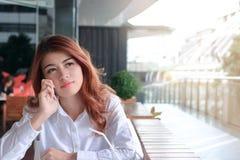 可爱的年轻亚裔女商人谈话在电话和等待的合作或者某人的画象咖啡馆的反对拷贝sp 库存图片