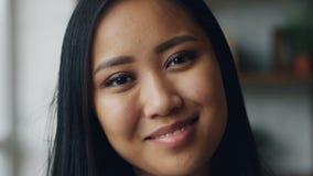 可爱的年轻亚裔妇女特写镜头慢动作画象有然后看与不显现表情的脸的完善的皮肤的照相机 股票视频