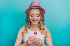 可爱的年轻人在她的手上拿着一个小桃红色棒棒糖 她看它和微笑 愉快的女孩 免版税图库摄影