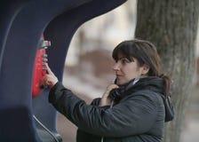 可爱的年轻女人叫从一个红色街道投币式公用电话 免版税库存图片