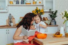 可爱的年轻女人和她的小逗人喜爱的女儿在厨房烹调 库存照片