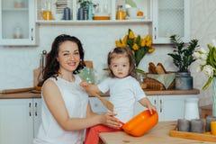可爱的年轻女人和她的小逗人喜爱的女儿在厨房烹调 免版税图库摄影