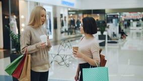 可爱的年轻女人在拿着多哥咖啡和纸袋有购买的购物中心谈话 时髦 影视素材