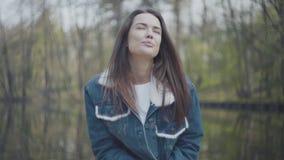 可爱的年轻女人画象坐河岸,看在照相机 与自然的连接 ?treadled 股票视频