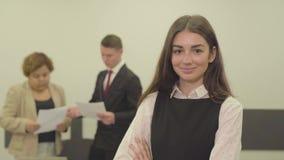 可爱的年轻女人画象看在前景的照相机的礼服的在办公室,当她的男性时 股票录像
