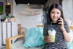 可爱的年轻女人谈话在手机在喝绿茶的咖啡馆,当坐有愉快的脸面护理的时沙发 库存图片