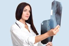 可爱的年轻女性专家画象放射学球形的学习人的` s骨骼X光芒, comapres某事,尝试t 免版税库存图片