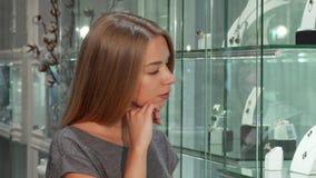 可爱的年轻女性在珠宝店的顾客审查的显示 股票录像