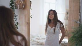 可爱的年轻女性获得在镜子前面的乐趣,站立在卧室 股票视频