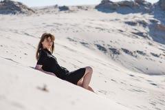 可爱的年轻女性被放置在沙漠沙丘 库存照片
